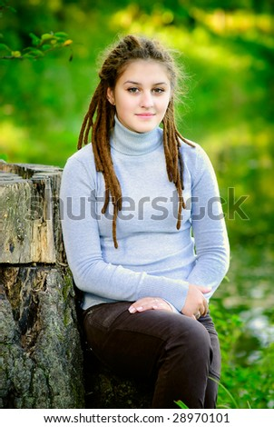 Young beautiful woman with hairdress dreadlocks against summer nature