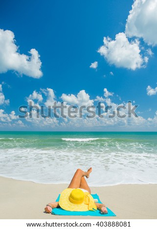 young beautiful woman with hat  relaxing on sand beach - stock photo