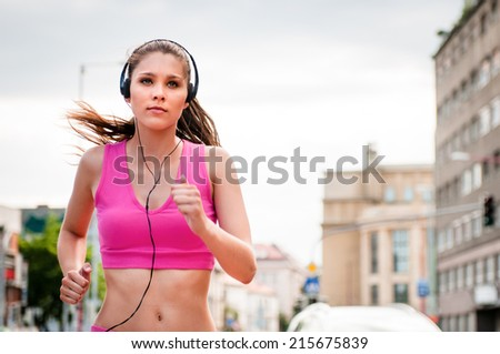 Young beautiful woman with headphones jogging and listening music in street - stock photo