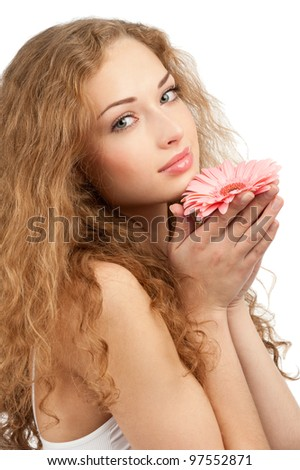 Young beautiful woman with healthy skin and long curly hair holding pink flower in her hands. Isolated on white background - stock photo