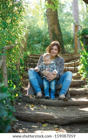 Young beautiful woman with her baby boy on the garden stairs - stock photo
