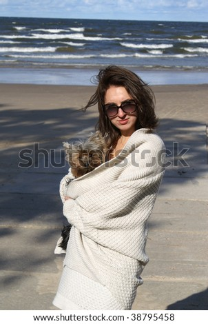 Young beautiful woman with her dog on a beach - stock photo