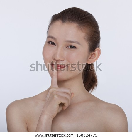 Young beautiful woman with her hands on her lips