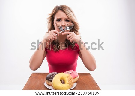 Young beautiful woman with knife and fork crossed at mouth sitting in front of doughnuts, diet concept, isolated on white background - stock photo
