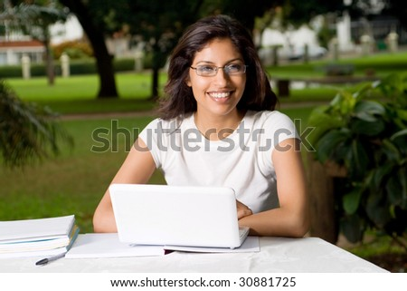 young beautiful woman with laptop and smiling - stock photo