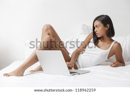 young beautiful woman with laptop on the bed - stock photo