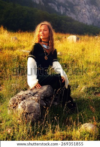 young beautiful woman with long blonde hair in black velvet medieval dress is sitting alone on a rock on a wild mountain meadow, looking up, with her face gently enlighted  - stock photo
