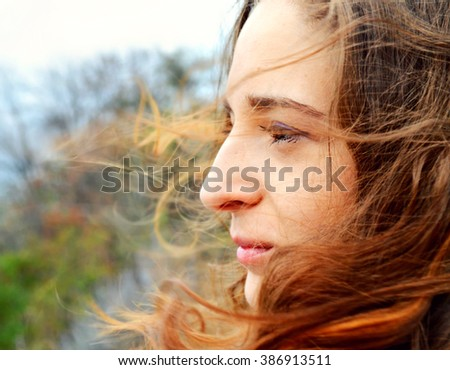 Young beautiful woman with long hair fluttering in the wind is smiling and looking at the horizon thinking - stock photo