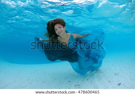 Young beautiful woman with long hair in a bright green-blue dress under water, underwater fashion in the Indian Ocean, Maldives