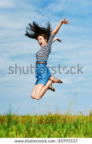 young beautiful woman with long hair on a summer day in the meadow jumping high - stock photo