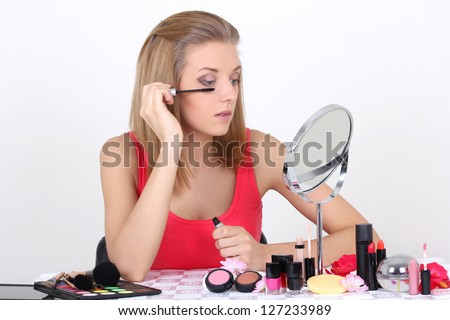 young beautiful woman with make up accessories and mirror - stock photo