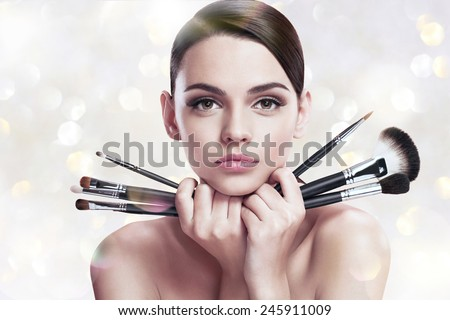 Young beautiful woman with makeup brushes near her face, skin care concept / photoset of attractive brunette girl on blurred background with bokeh  - stock photo