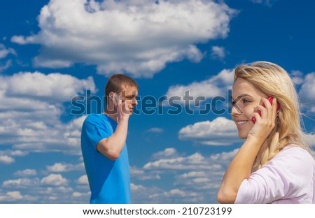 Young beautiful woman with man talking on mobile phone against blue summer sky. - stock photo
