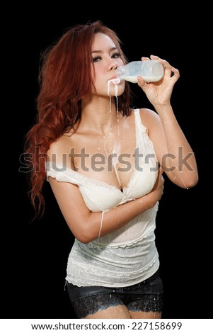 young beautiful woman with milk, isolated on black - stock photo