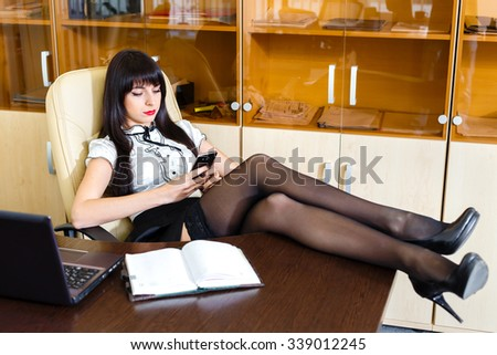 Young beautiful woman with mobile phone in office