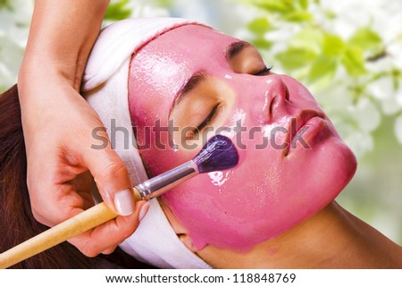 Young beautiful woman with moistening fruit facial mask at beauty salon