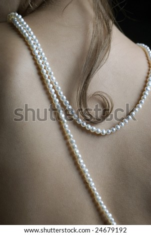 Young beautiful woman with natural water pearls hanging on her back - stock photo