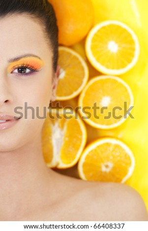 Young beautiful woman with oranges on background