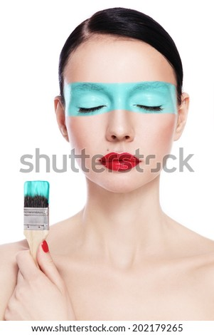 Young beautiful woman with painting brush and paint on her face over white background - stock photo