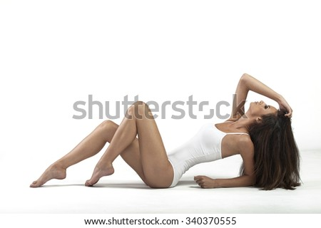 Young beautiful woman with perfect body in cotton underwear sitting on white background - stock photo