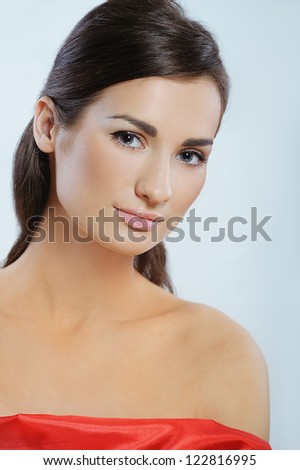 Young beautiful woman with perfect health skin  in red dress - stock photo