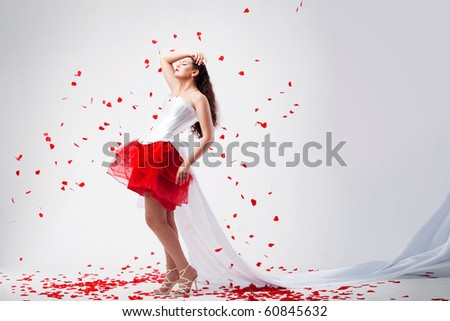 young beautiful woman with petals of roses, on a white background