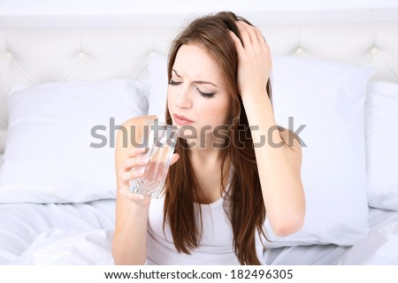 Young beautiful woman with pills on bed close-up