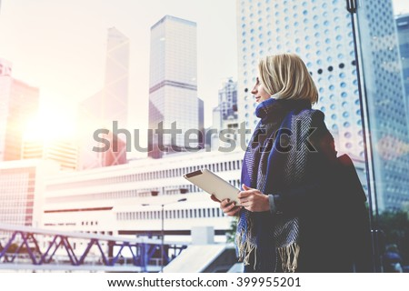 Young beautiful woman with portable touch pad in hands is enjoying view of New York business center outside the window background with copy space for advertising text message or promotional content - stock photo