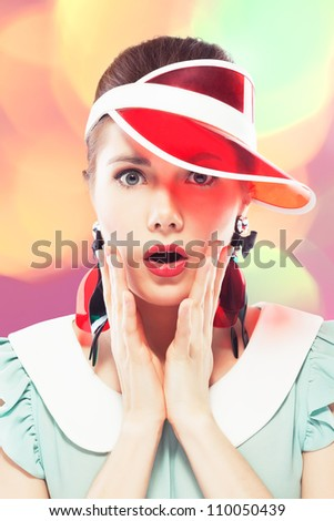 Young beautiful woman with red glamour lips and eye arrow make-up wearing fancy plastic earrings and red sun visor on multicolor background, she is open-mouthed with surprise, retro beauty style - stock photo