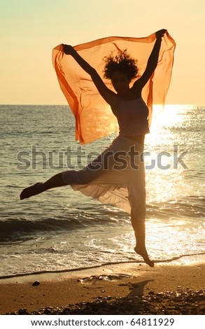Young beautiful woman with red handkerchief jumping on beach. sunlight glare on water
