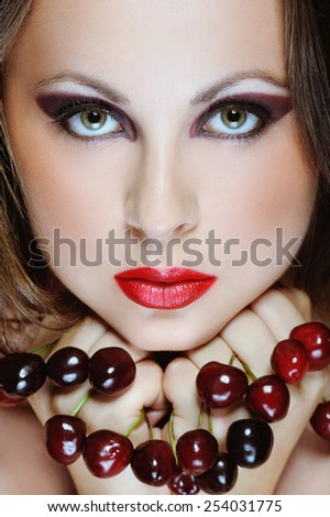 Young beautiful woman with red lips and cherries in her hands - stock photo