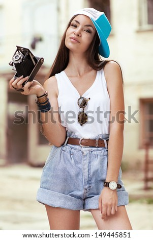 Young, beautiful woman with retro camera. Beautiful girl hipster filming. - stock photo