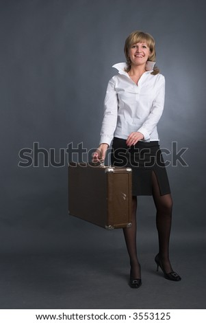 young beautiful woman with retro suitcase on grey background - stock photo