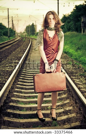 Young beautiful woman with retro suitcase standing on a railway and looking on camera. Emotional retro concept