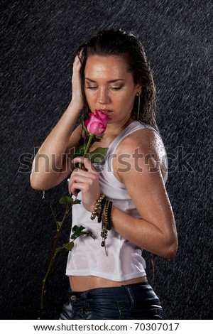 Young beautiful woman with rose stands under rain on a black background. - stock photo