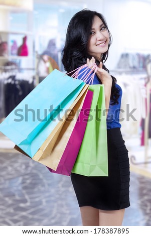Young beautiful woman with shopping bags in shopping center - stock photo