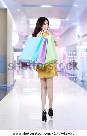 Young beautiful woman with shopping bags in shopping center