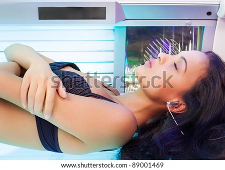 Young beautiful woman with slim body lying in tanning bed - stock photo