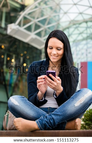 Young beautiful woman with smartphone - outdoor lifestyle portrait