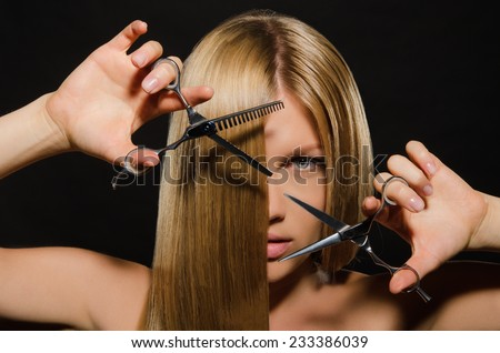 Young beautiful woman with straight hair and scissors on black background