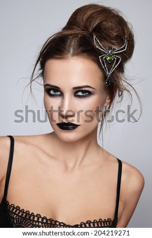 Young beautiful woman with stylish gothic make-up and hairdo - stock photo