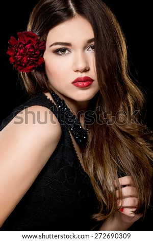 Young beautiful woman with stylish make-up and red flower in her hairstyle. Spanish woman