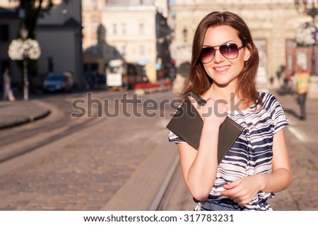 Young beautiful woman with sunglasses walking in the old european morning town with a book and smiling