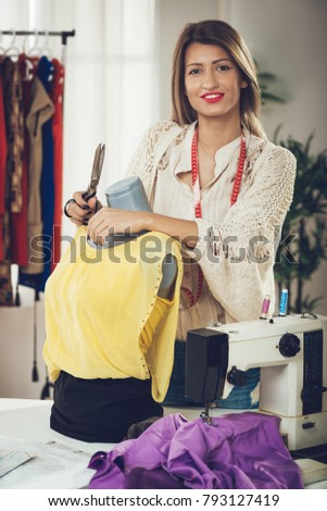 Young beautiful woman with tape measure draped over neck standing at the work place leaning against the dressed mannequin and with a smile looking at the camera.