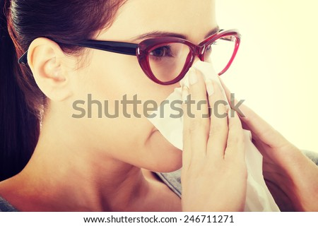 Young beautiful woman with tissue having runny nose. - stock photo