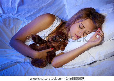 young beautiful woman with toy bear sleeping on bed in bedroom - stock photo