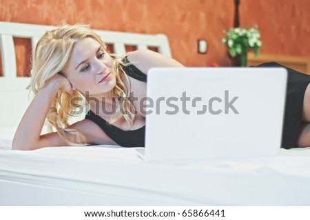 Young beautiful woman with white laptop in luxury room