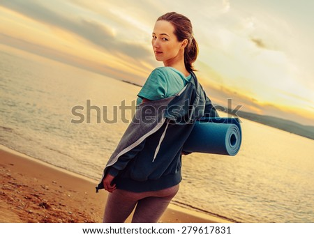 Young beautiful woman with yoga mat standing on beach in summer at sunset and ready for workout - stock photo