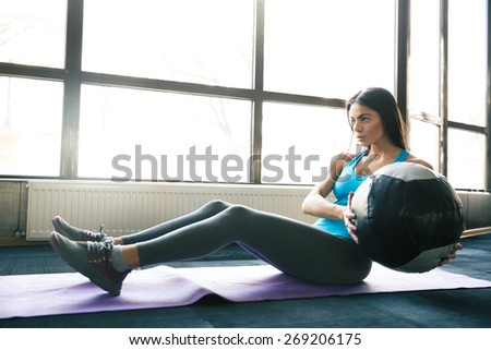 Young beautiful woman working out with fit ball on yoga mat at gym - stock photo