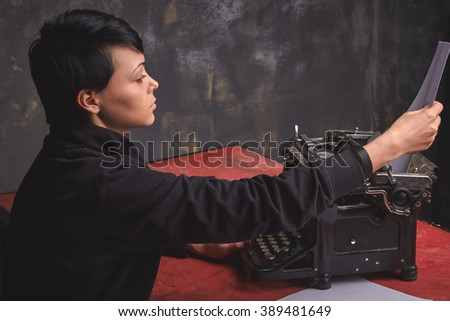 Young  beautiful woman writer in dark wear, creative process of making story on retro typewriter in art space with dark background - stock photo